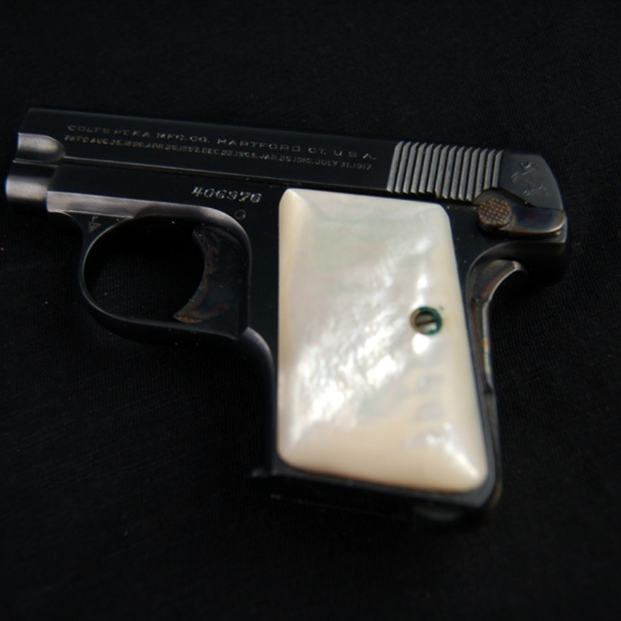colt 25 caliber pistol with a mother of pearl handle and holster ebth