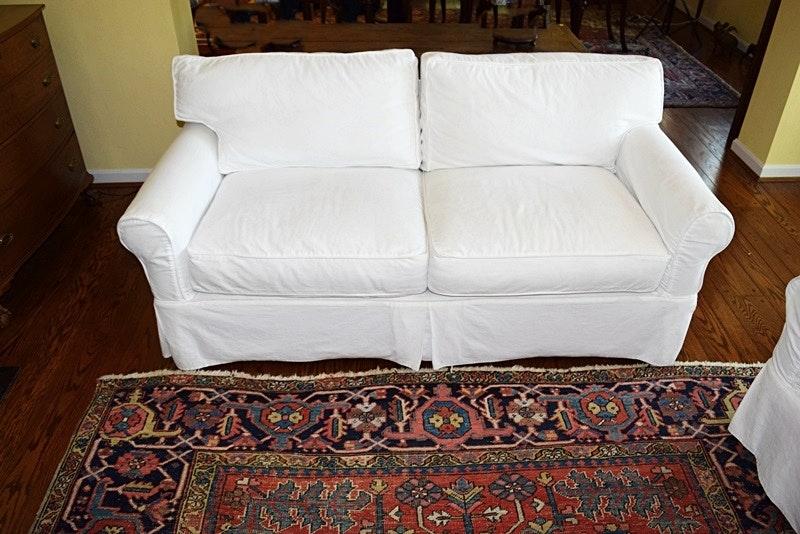 An Arhaus Two Cushion Sofa With White Canvas Slipcover