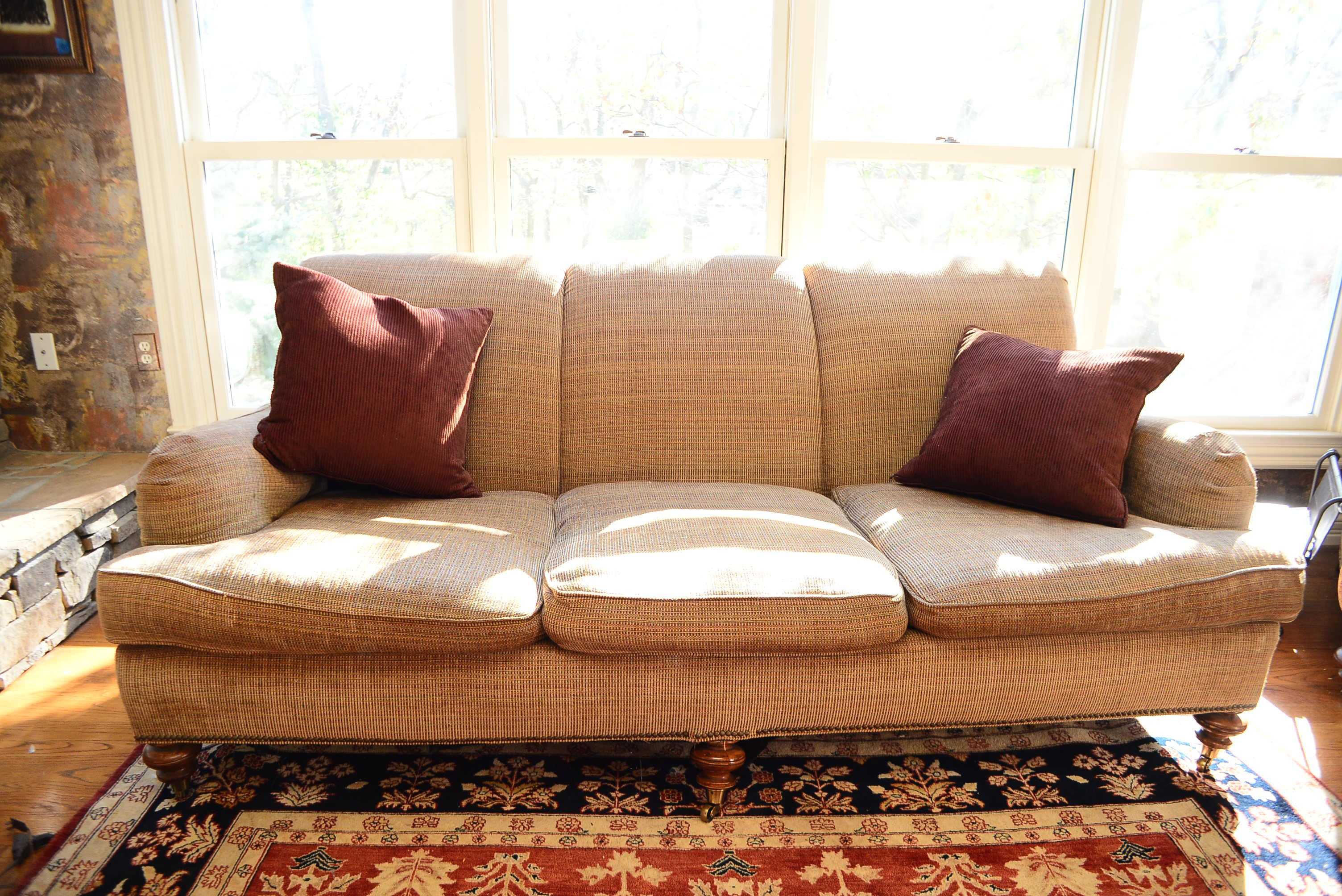 Caramel Sofa With Wood And Caster Legs And Plush Pillows ...