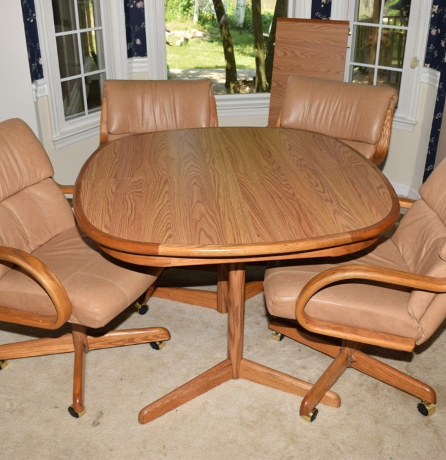 Oak kitchen table and four leather and oak swivel chairs for Leather kitchen table chairs