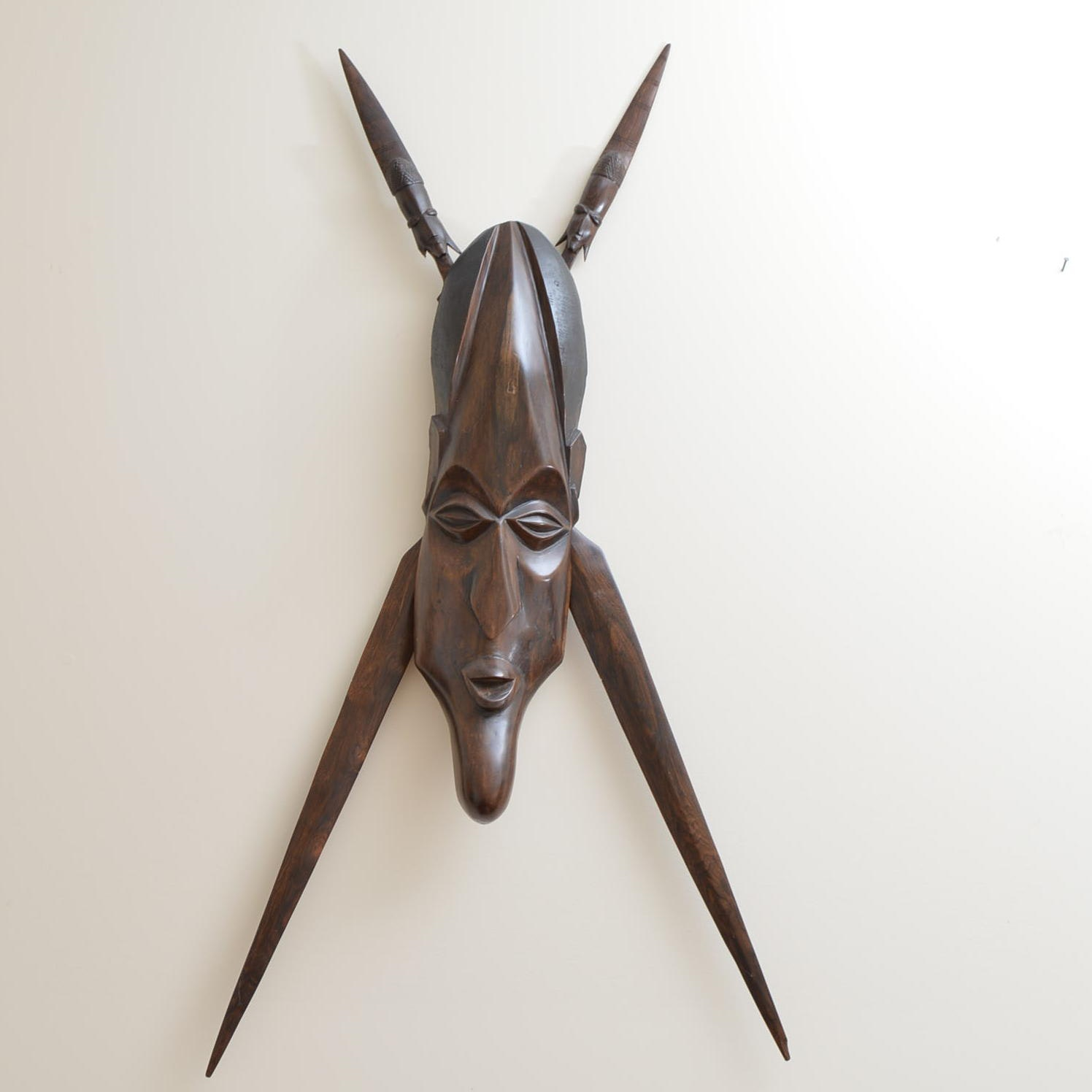 Carved Wood Elongated Face With Crossed Spears