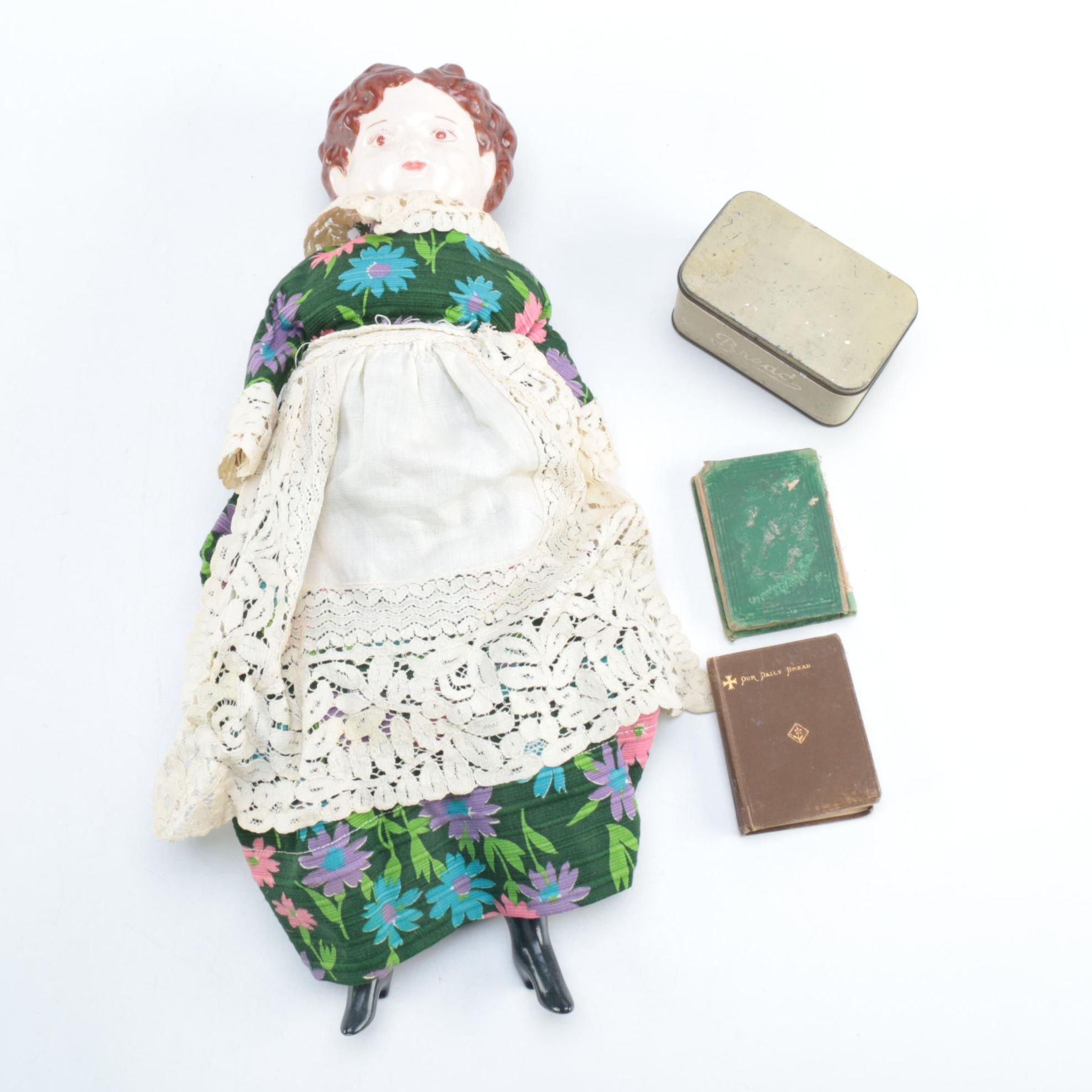 Porcelain Doll with Religious Books and Tin Container