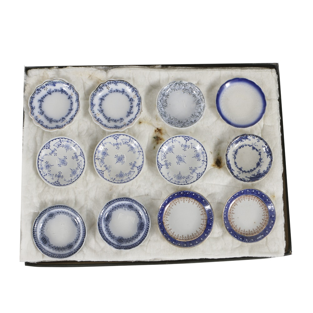 Twelve Porcelain Butter Pats In Glass Top Display Case