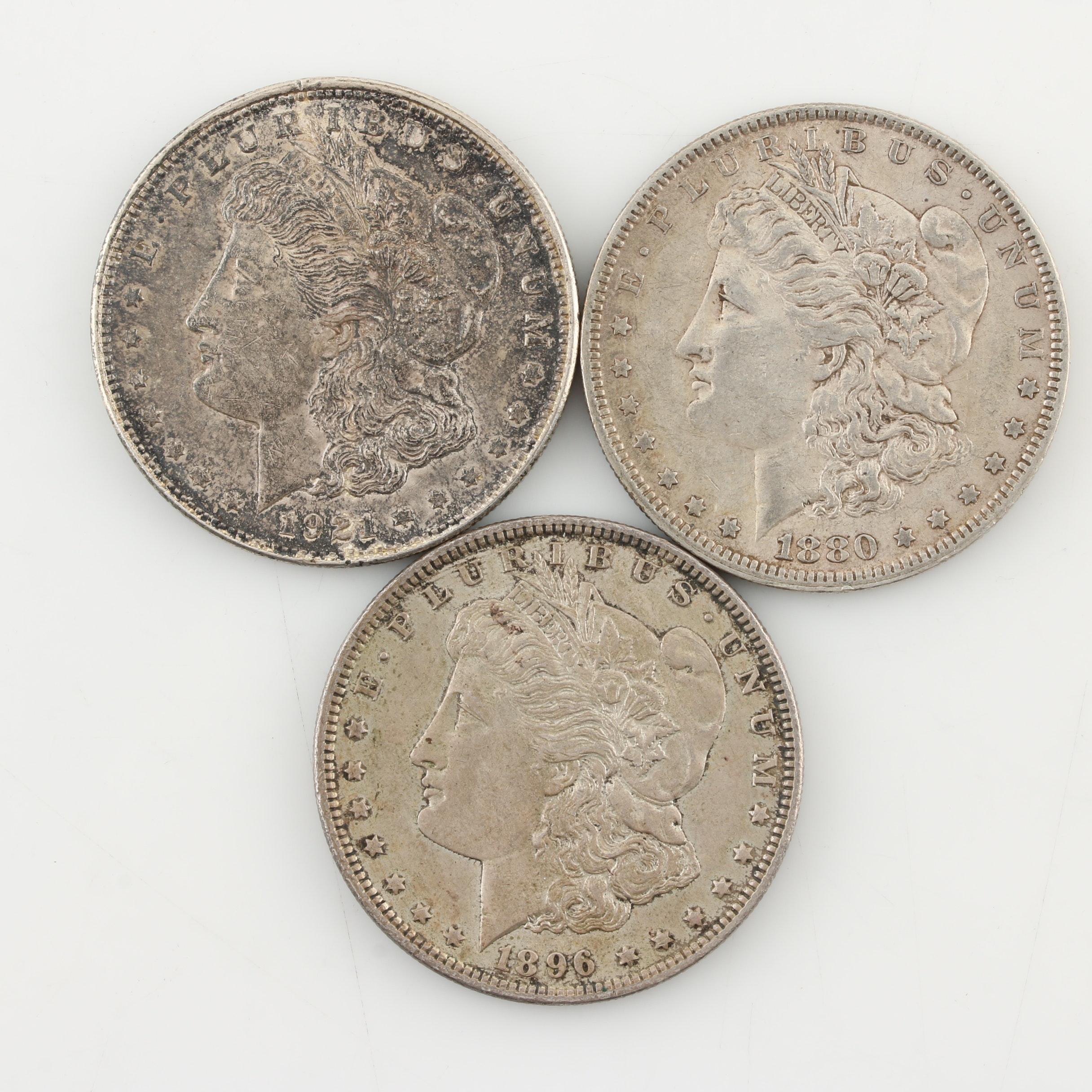 Three Morgan Silver Dollars: 1880-O, 1896, and 1921