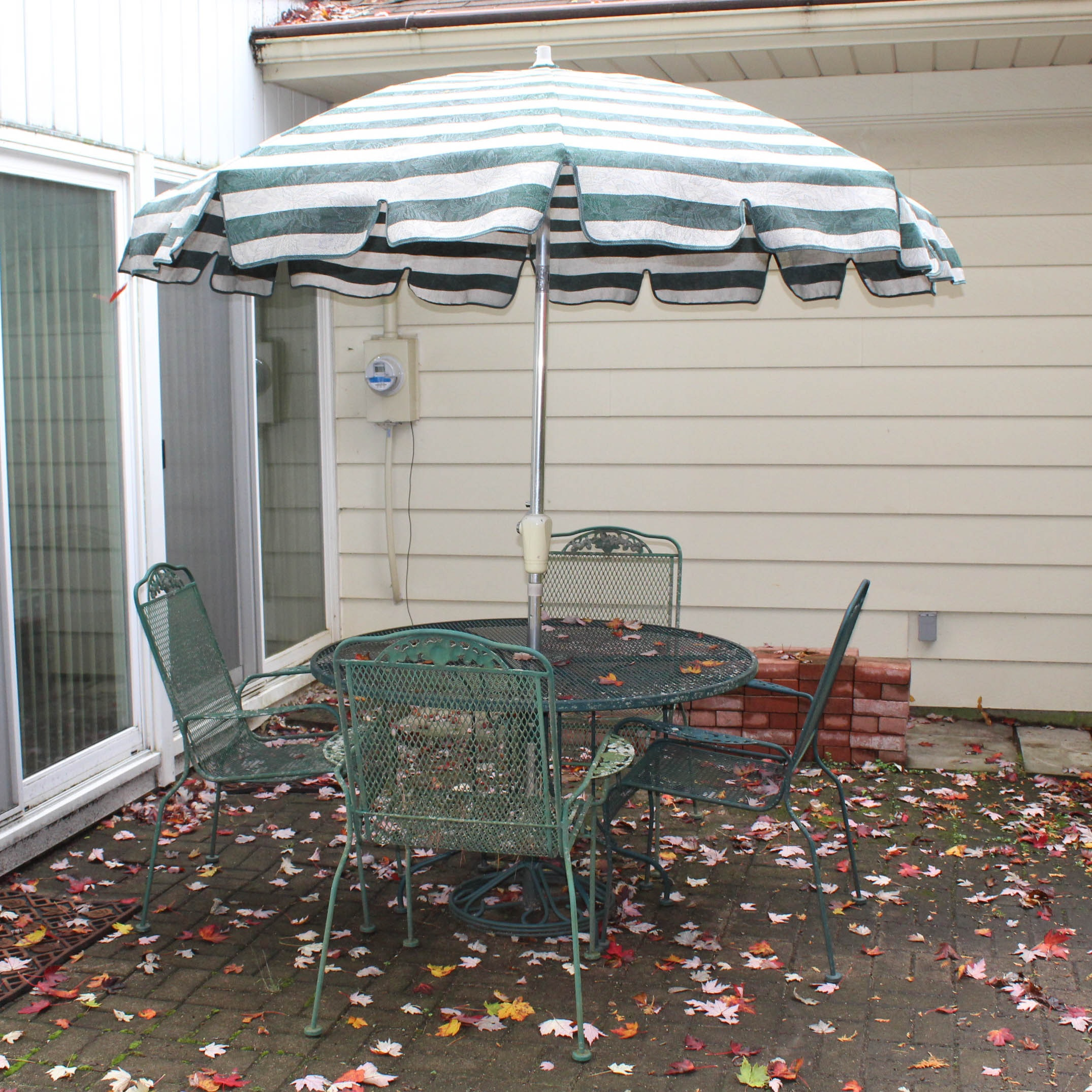 Green Metal Patio Table with Umbrella and Four Chairs