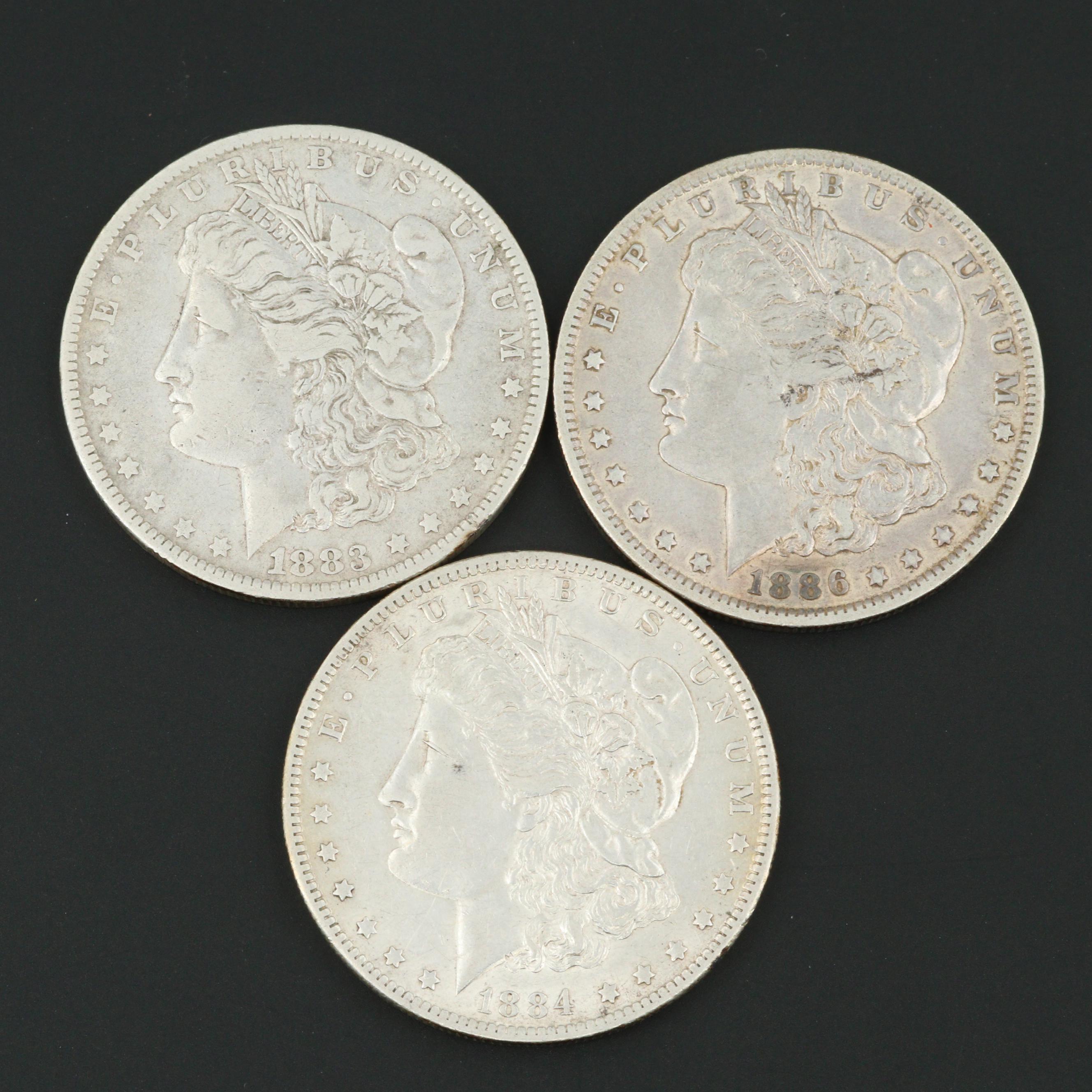 Three Silver Morgan Dollars Including 1883-O, 1884-O, and 1886-O