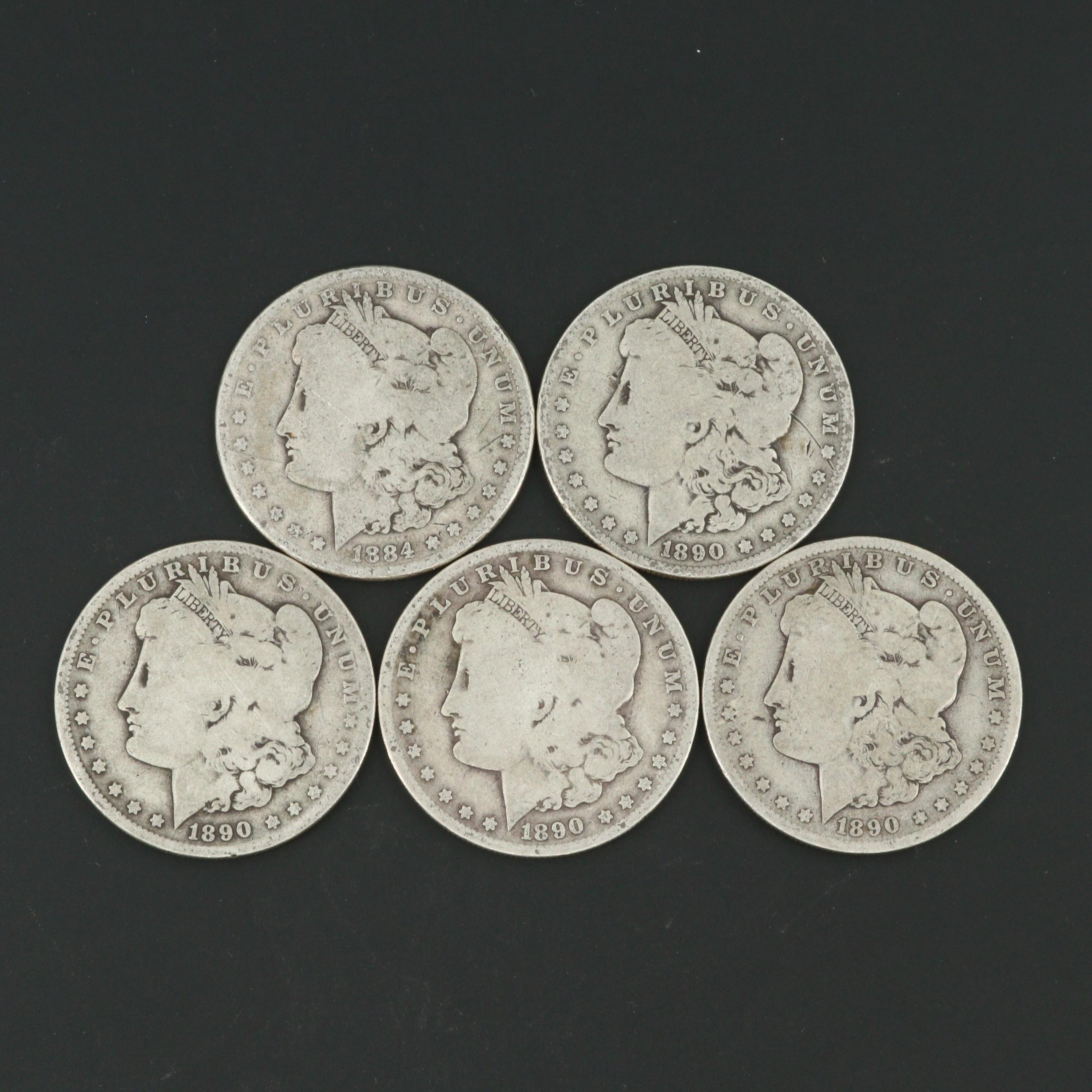 One 1884 and Four 1890-O Morgan Silver Dollars