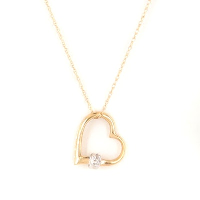 18K Yellow Gold Diamond Heart Pendant Dangling From 14K Yellow Gold Neck Chain