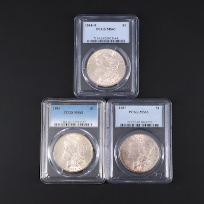 Three PCGS Graded MS63 Silver Morgan Dollars Including 1884-O, 1886, and 1887