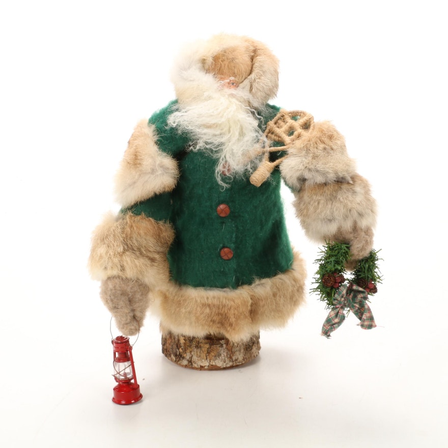 Santa on Wooden Base with Lantern, Wreath, Snowshoes, and Bag of Gifts Figurine